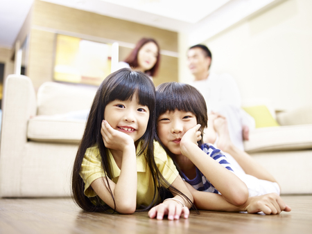asian brother and sister lying on front on floor with parents in the background.
