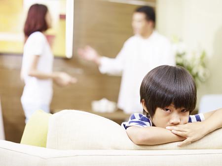 Aziatisch kind lijkt verdrietig en ongelukkig terwijl ouders op de achtergrond ruzie maken.