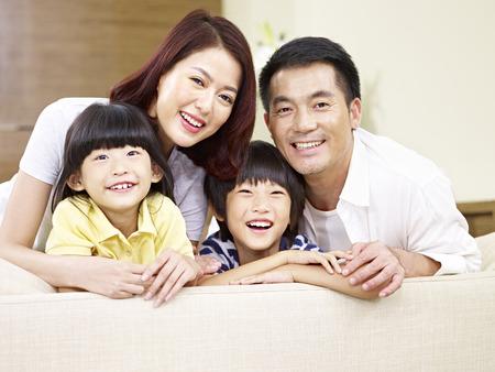 portret van een Aziatisch gezin met twee kinderen, blij en lachend.