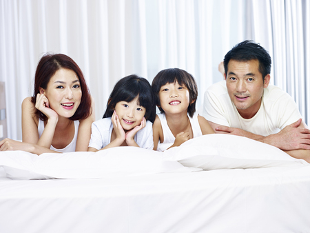 happy asian family with two children lying on front in bed looking at camera smiling.