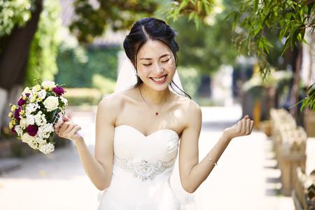 若くて美しいアジアの花嫁はブーケを手に歓喜します。