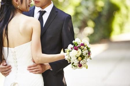 アジア結婚式のカップルは、お互いをハグ花束に焦点を当てる。