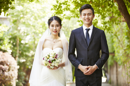 outdoor portrait of asian bride and groom looking at camera smiling.