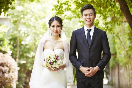 아시아 신부와 신랑의 미소를 카메라를 찾고 야외 초상화. 스톡 콘텐츠
