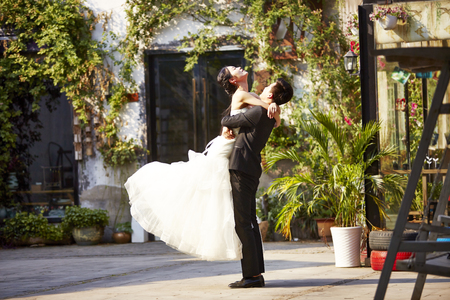 asian newly wed bride and groom celebrating marriage outside a building.