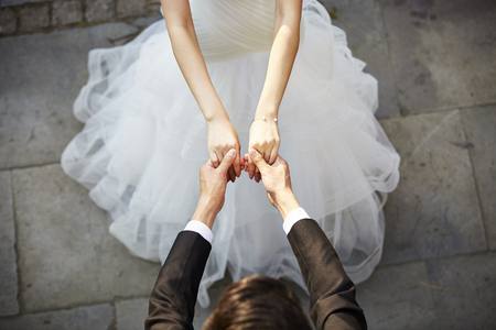 young asian bride and groom holding hands and dancing, high angle view.