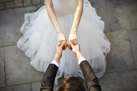 jonge Aziatische bruid en bruidegom hand in hand en dansen, high angle view.
