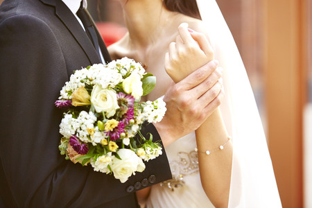 loving bride and groom with bouquet hugging each other at wedding day