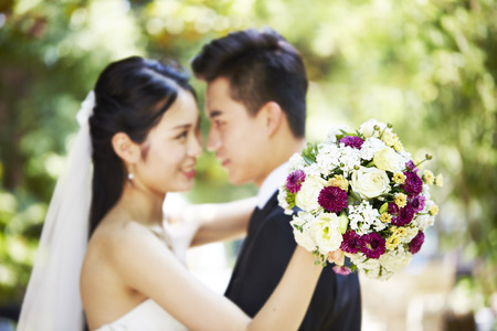young asian newly wed couple hugging each other during wedding ceremony, focus on the bouquet.