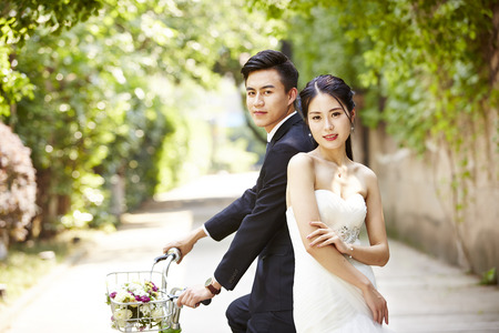 newly-wed asian bride and groom taking picture with a bicycle.