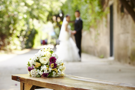 bouquet on wooden bench with bride and groom in the background, focus on the flowers.