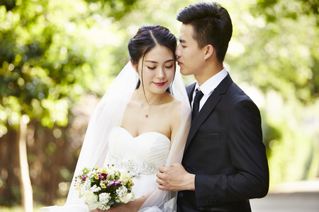 jonge Aziatische bruidegom kussende bruid buitenshuis tijdens huwelijksceremonie.