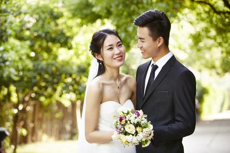 アジアの花嫁と花婿の幸せと笑顔の屋外のポートレート。 写真素材
