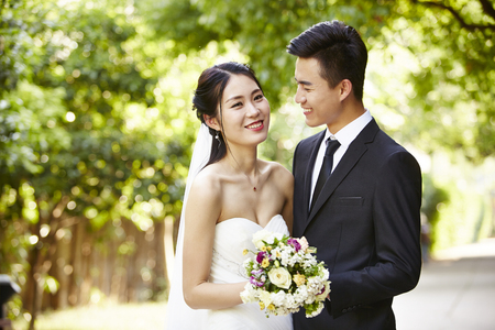 outdoor portrait of asian bride and groom, happy and smiling.