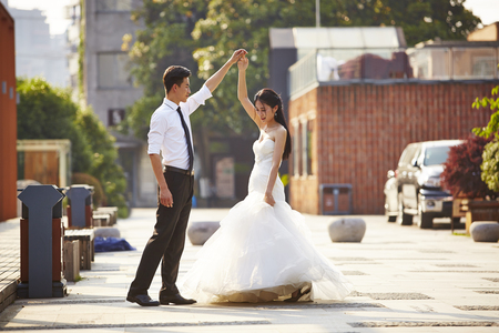 young asian bride and groom in wedding dress dancing in parking lot. Archivio Fotografico