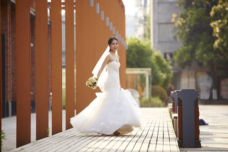 outdoor portrait of young and beautiful asian bride with bouquet in hand. Stock Photo