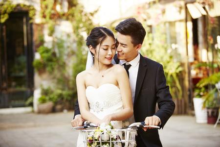 新しく結婚したアジアのカップルが自転車に乗って楽しんで幸せ。