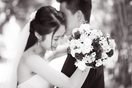 young asian newly wed couple hugging each other during wedding ceremony, focus on the bouquet, black and white.
