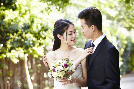 若いアジアの新郎は屋外の結婚式の時に花嫁をキスします。 写真素材