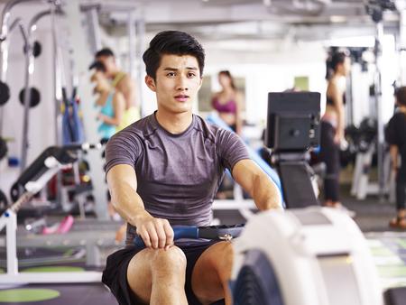 若いアジアの大人の男はローイング マシンを用いたジムでワークアウトします。