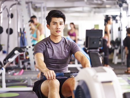 young asian adult man working out in gym using rowing machine. Archivio Fotografico