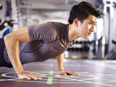 young asian adult man exercising in gym doing push-ups, side view.
