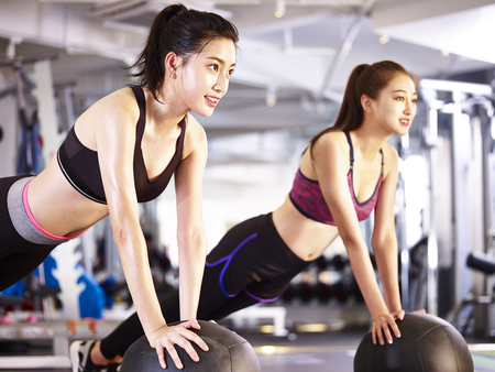 two young asian adult women working out in gym using medicine balls.