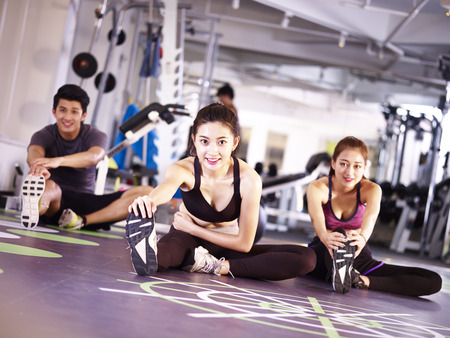 3 アジア アダルト若者は足を伸ばしジムで運動。