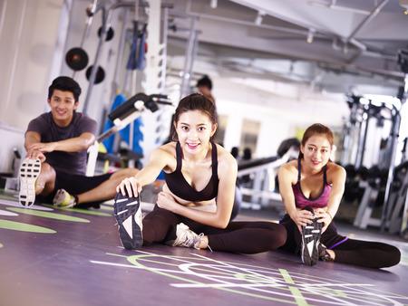 drie jonge Aziatische volwassen mensen die in gymnastiek uitrekkende benen uitoefenen. Stockfoto