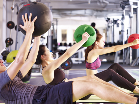 three young asian adult people working out in fitness center using medicine balls. Imagens