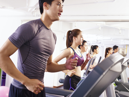 young asian adult working out on treadmill, focus on the girl in the middle.