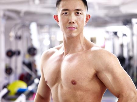 Retrato de un joven culturista asiático en el gimnasio.