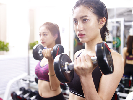 two young asian women working out exercising in gym using dumbbells.