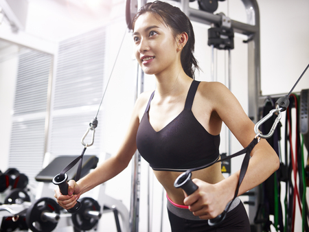 젊은 아시아 여자 운동 장비를 사용 하여 체육관에서 밖으로 작동합니다.
