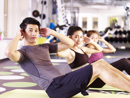 three young asian adults, male and female, doing sit-ups on the floor in gym. Stockfoto