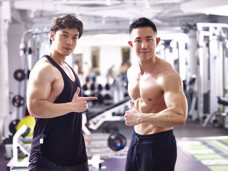 two asian bodybuilders posing in gym showing muscles.