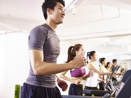 若いアジアの大人はトレッドミルでワークアウトします。 写真素材