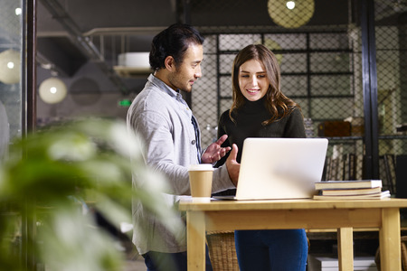 asian business man and caucasian business woman having a discussion in office using laptop computer.