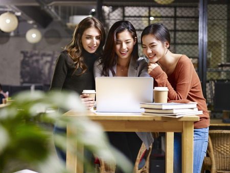 three happy businesswomen asian and caucasian using laptop computer together.