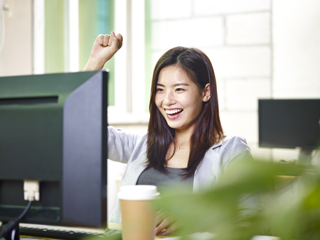 young asian business woman working in office using desktop computer, happy and excited at good news.