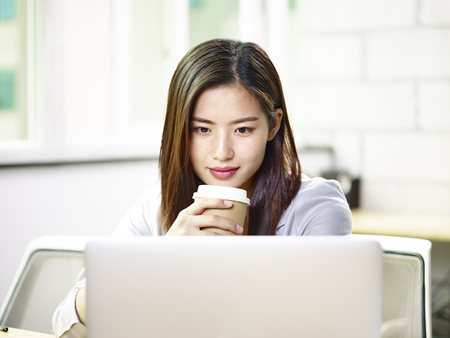 beautiful young asian business woman working in office holding a cup of coffee looking at laptop computer. Stock Photo