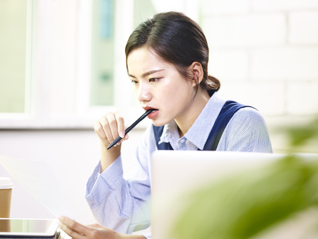 young asian woman corporate executive analyzing a report in modern office.