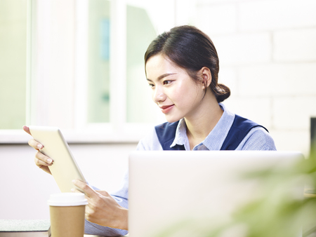 young asian business woman working in office using laptop computer and digital tablet.