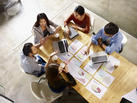 high angle view of a team of asian and caucasian corporate executives discussing business in meeting room. Stock Photo