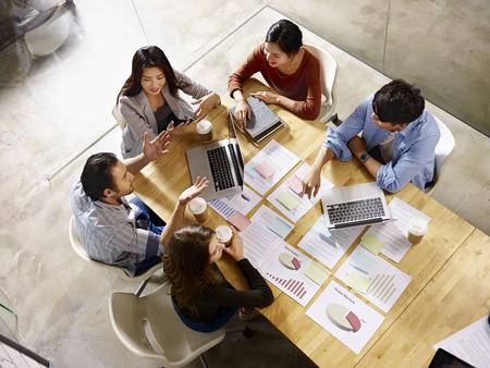 hohe Winkelsicht eines Teams der asiatischen und kaukasischen Unternehmensleiter, die Geschäft im Konferenzzimmer besprechen. Standard-Bild