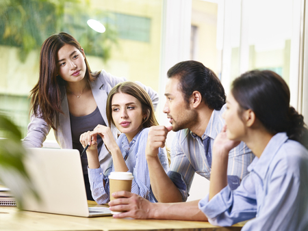 team of young asian and caucasian entrepreneurs male and female meeting in office discussing business using laptop computer.
