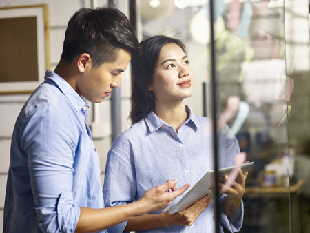 young asian businessman and businesswoman working together making a business plan using adhesive notes in office. Archivio Fotografico