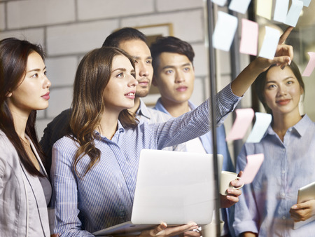 team of young asian and caucasian entrepreneurs discussing business using laptop, digital tablet and adhesive notes in office. Stock Photo - 91431270