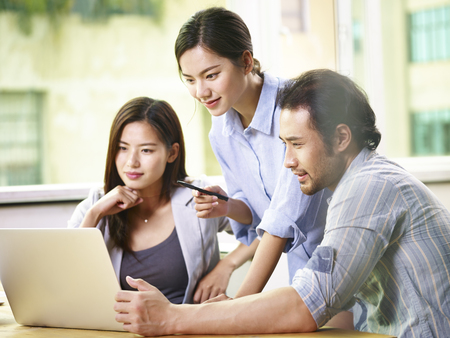 team of young asian business people in casual wear working together in office using laptop computer. Stockfoto