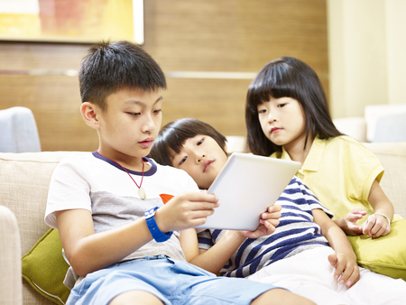 three asian children two little boy and one little girl lying on couch lazily playing video game with digital tablet. Archivio Fotografico